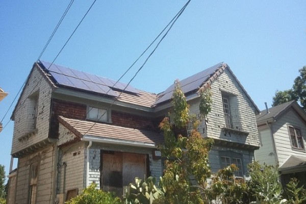 Solar panels on a building with a boarded window
